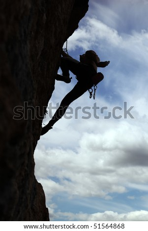 Silhouette of rock climber climbing a cliff with cloudy sky background