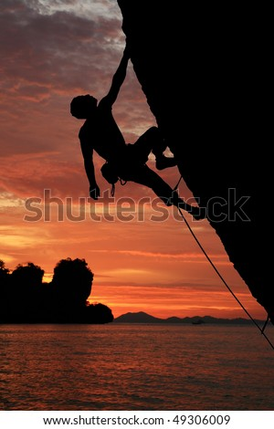 silhouette of rock climber climbing an overhanging cliff with sunset over the ocean background