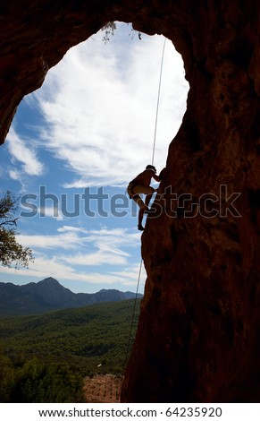 Silhouette of rock climber climbing the cliff