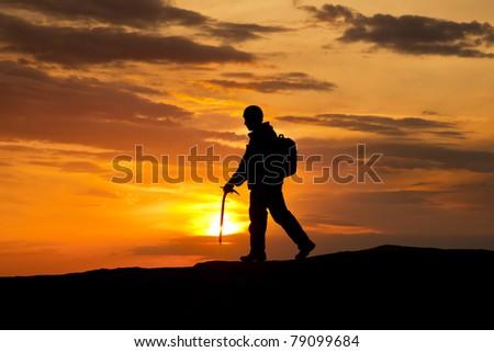 silhouette of rock climber on sunset sky - stock photo