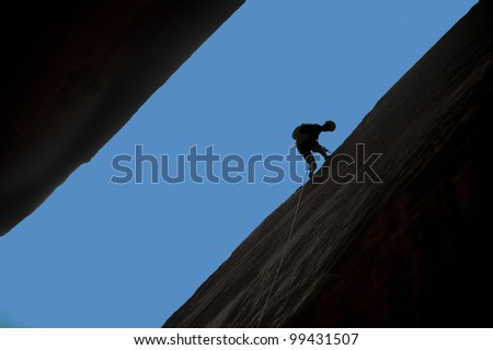 Silhouette of rock climber rappelling a crack with blue sky behind.