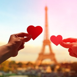 silhouette of romantic lovers hand hold love heart paper with eiffel tower in Paris with sunset