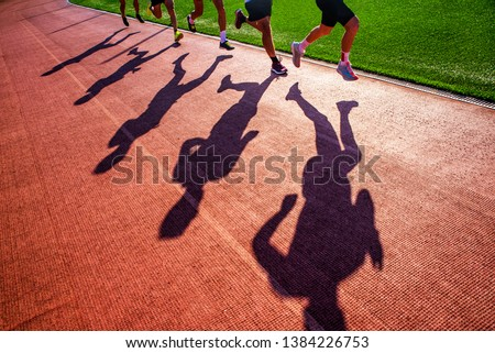 Silhouette of runners who race together in group on the athletics track. Track and Field photo #1384226753