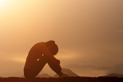 silhouette of sad and depressed woman sitting on top of mountain with sunrise