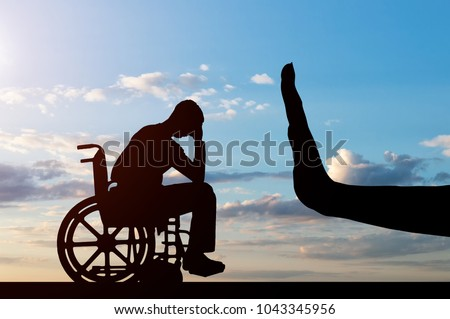 Silhouette of sad disabled man in wheelchair and hand gesture stop. The concept of discrimination and disrespect for people with disabilities