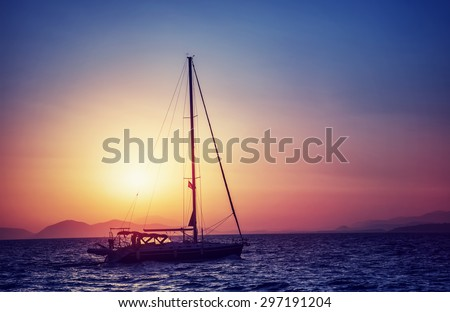Silhouette of sailboat on sunset, water transport in bright yellow sun light, sea trip in the evening, traveling around Greek islands