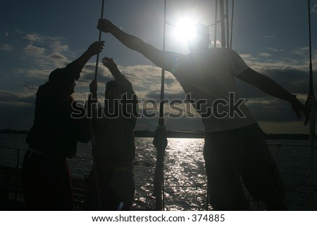 Silhouette of sailors setting sail on a schooner sailing ship.