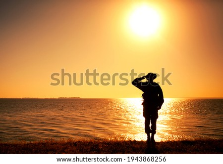 Silhouette of saluting commando soldier, army infantryman standing on shore during sunset or sunrise. Military solemn ceremony, respectable salute for honoring fallen heroes and comrades veterans Stock photo ©