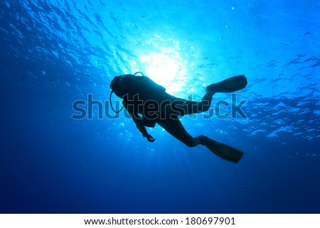 Silhouette of scuba diver and sunlight in the blue water #180697901
