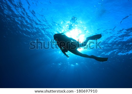 Silhouette of scuba diver and sunlight in the blue water #180697910