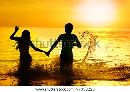 Silhouette of sea bathing of young couple against sunset.