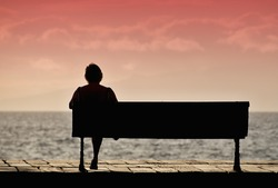 Silhouette of senior woman sitting alone on the bench in front of the sea