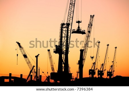 Silhouette of several cranes in a harbor, shot during sunset