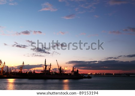 Silhouette of several cranes in a harbor, shot during sunset. Odessa, Ukraine
