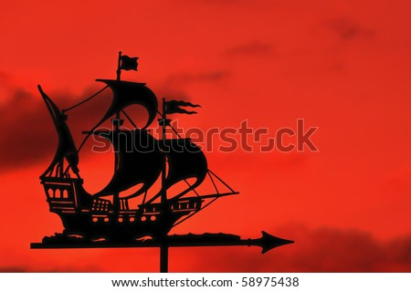 stock photo : Silhouette of Ship Weather Vane against a Red Sky at Sunset