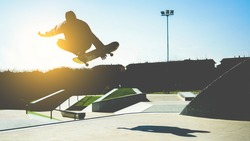 Silhouette of skater jumping on ramp at city park - Young man performing tricks and skills with skateboard at sunset  - Youth,extreme sport concept - Focus on body - Vintage retro filter