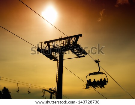 Silhouette of ski lift infrastructure with skier.