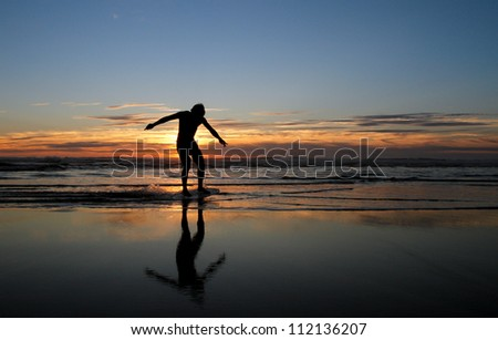 silhouette of skimboarder in sunset