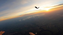 Silhouette of skydivers at sunrise