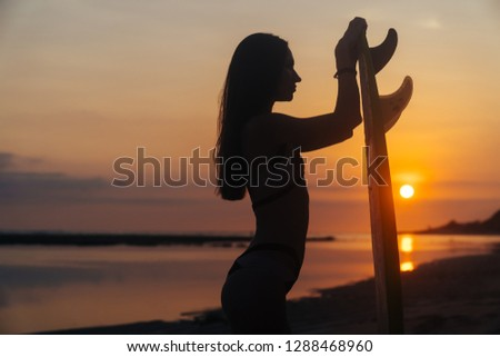 Silhouette of slim girl with surfboard in hands at beach on background of beautiful sunset. Woman go to surfing. Concept of active lifestyle, sport