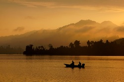Silhouette of small fishing boat with sunrise in the background