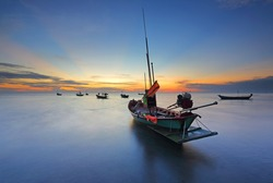 Silhouette of small fishing boats parked on a quiet sea. long movement with sunrise at Chao Lao Beach, Chanthaburi, Thailand