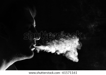 Silhouette of smoker exhales smoke