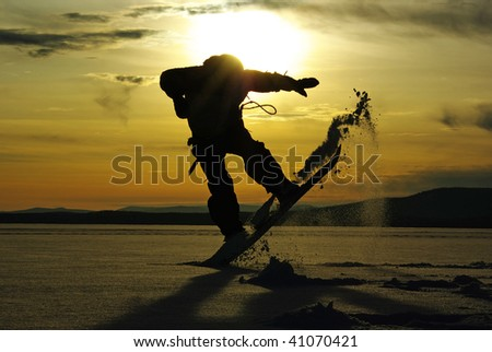 Silhouette of snowboarder jumps in powder