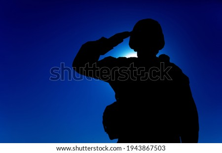 Silhouette of soldier in combat helmet and ammunition saluting on background of sunset sky. Army special forces fighter, Marines rifleman showing respect, greeting officer with salute gesture Stock photo ©