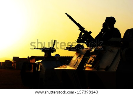Silhouette of soldier with machine gun on a car against a sunset
