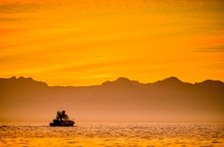 Silhouette of Speed boat in the ocean at sunset. Boating at sunset in Atlantic ocean, South Africa