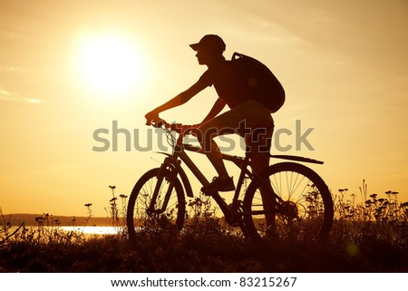 Silhouette of sports person cycling on the field on the beautiful sunset
