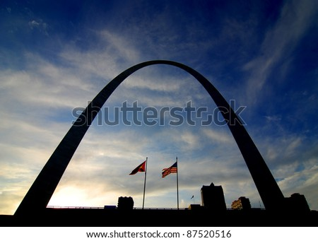 Silhouette of St. Louis Arch and city skyline with flags, sky and clouds