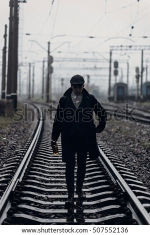 silhouette of stylish man in retro look walking in rain on background of foggy railway. england in 1920s theme. fashionable brutal gangster. atmospheric  moments. space for text