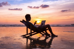 silhouette of successful business man reading emails on laptop on the beach at sunset, freelance job concept, work abroad