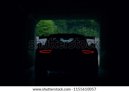 Stock Photo Silhouette of supercar in tunnel with stop lights. Back view of supercar