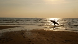 Silhouette of surf man with surfboard running on water surface. Surfing at sunset beach. Outdoor water sport adventure lifestyle.Summer activity. Handsome Asia male model in his 20s.