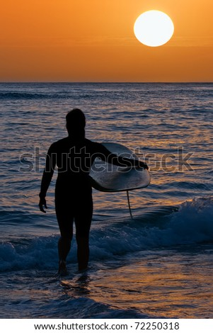 Silhouette of surfer at sunset at Waikiki Beach on Oahu, Hawaii.