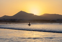 Silhouette of surfer on Famara beach with the sun hiding behind the mountain