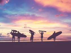 Silhouette Of surfer people carrying their surfboard on sunset beach, vintage filter effect with soft style