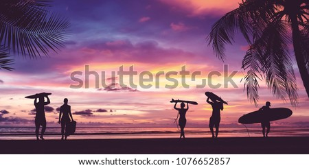 Silhouette of surfer people carrying their surfboards on sunset beach. Panoramic soft style with vintage filter effect for banner background.