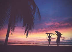 Silhouette of surfer people carrying their surfboards on sunset beach, vintage filter effect