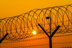 Silhouette of surveillance camera and barbed wire fence steel jail with the sunset in the background