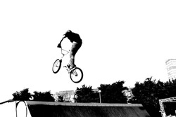 Silhouette of talented young man freestyler riding off road sport bicycle in skatepark, doing stunts, flying over ramp. Monochrome outdoor picture of unrecognizable rider jumping in summer park