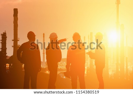 Silhouette of Teams engineer and foreman working at petrochemical oil refinery in sunset
