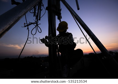Silhouette of Technician working on communication towers in the dusk #535213534