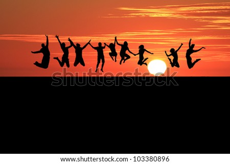 silhouette of teenagers jumping on beach in sunset