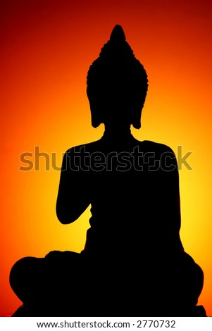 Silhouette of Thai style buddha with candle-light background