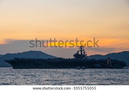 Silhouette of the aircraft carrier USS Ronald Reagan on a mission to Hong Kong during sunset