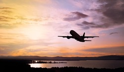 Silhouette of the airplane flying in the colorful sunset sky over the mountains and water area